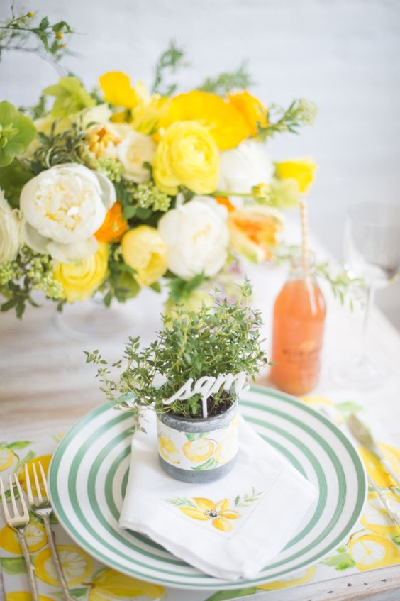 a bright spring tablescape with citrus placemats, striped plates, bold blooms and potted greenery with a calligraphy topper