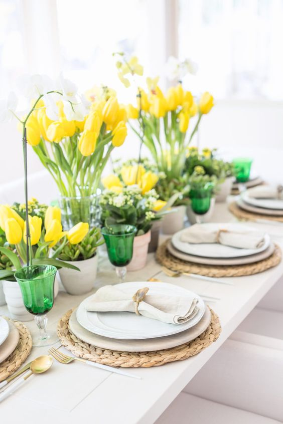 a bright spring tablescape with yellow tulips, green glasses, woven chargers, neutral plates, green glasses and white orchids