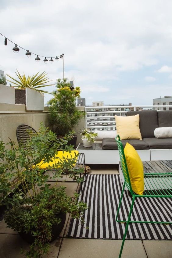 a bright spring terrace in trendy yellow and grey, with a striped rug, cool modern furniture and potted greenery