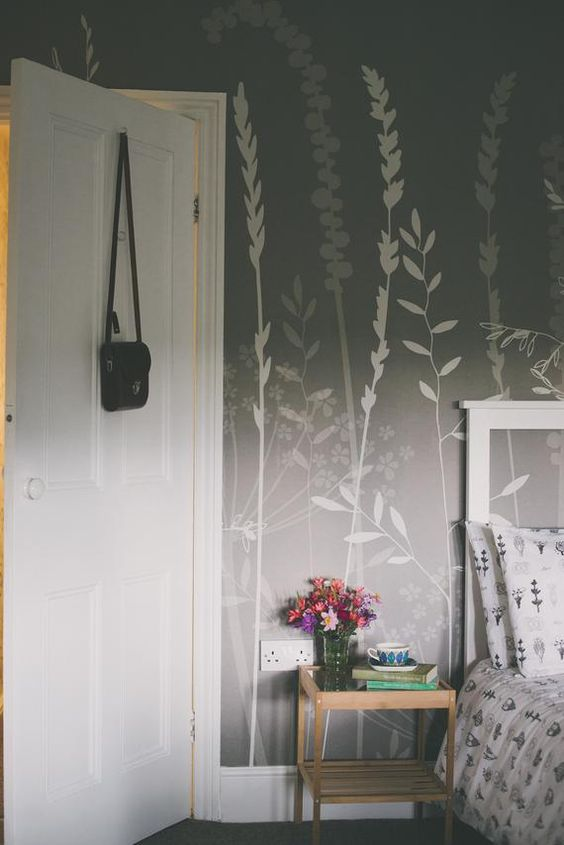 a calming and relaxing bedroom with grey and white botanical wallpaper that makes an accent and adds catchiness to the space
