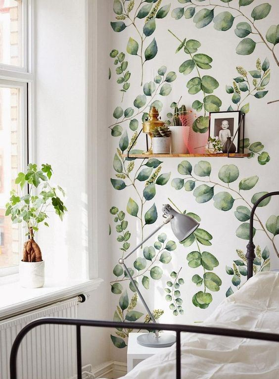 a calming and welcoming bedroom with leafy print wallpaper, a metal bed, a vintage lamp and a shelf plus some potted greenery