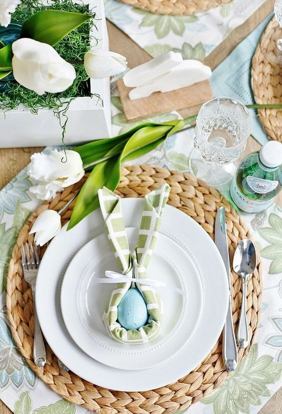 a chic Easter table setting with botanical placemats, woven chargers, pastel napkins, white tulips and eggs