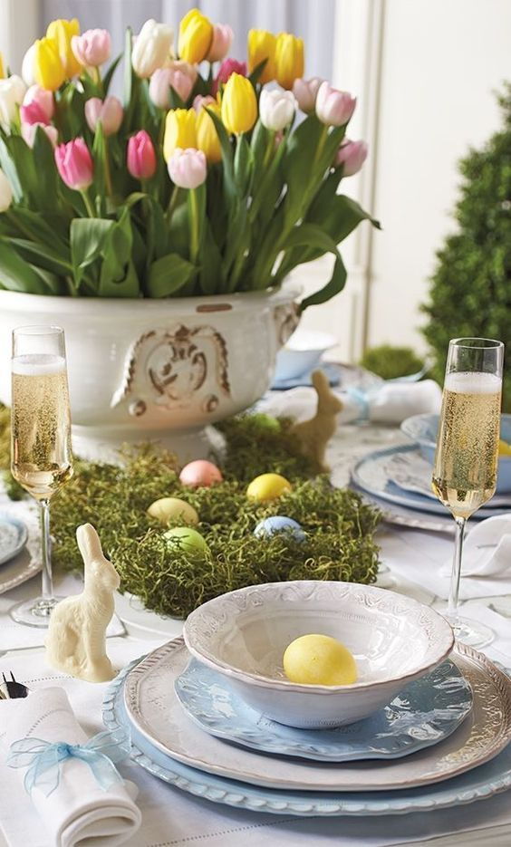 a chic Easter tablescape with a bold tulip centerpiece, moss with colorful eggs, blue porcelain and eggs