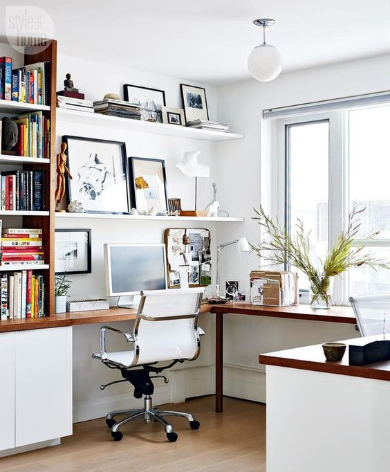 a chic Scandinavian home office with a corner desk, open shelves for storage and cabinets, some greenery and art