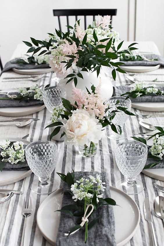 a chic and simple spring tablescape with a striped runner, grey napkins, white and pink blooms and refined glasses