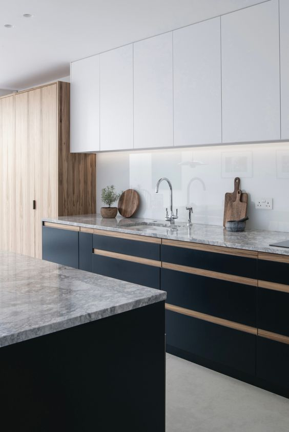 a chic contemporary kitchen with white and black cabinets, stained wooden cabinets, a white glass backsplash and stone countertops