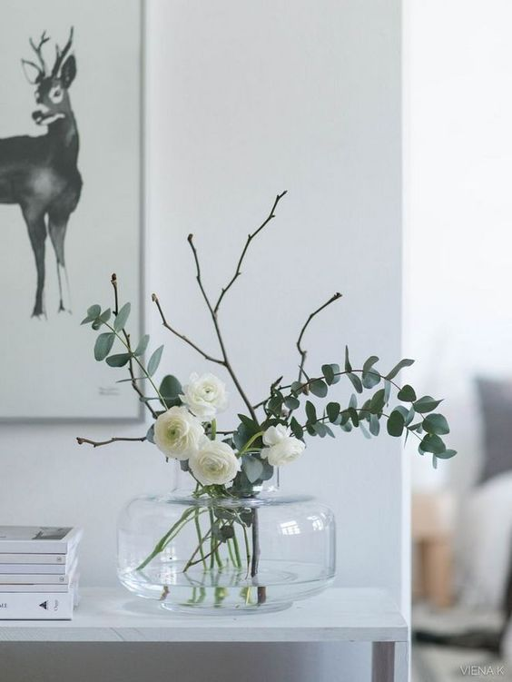 a chic glass vase with white blooms, twigs and eucalyptus is a lovely idea for spring, can be used as centerpiece or just arrangement