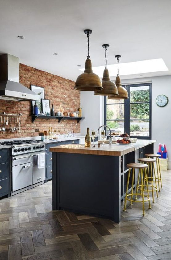 a chic kitchen with navy cabinets, a navy kitchen island with a butcherblock counter, a brick accent wall and retro pendant lamps