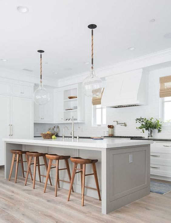 a chic kitchen with white cabinets, a grey kitchen island, wooden stools, black and white countertops and pendant lamps