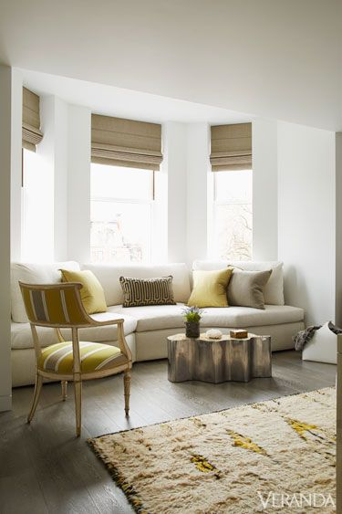 a chic neutral space with a bay window and a fitting sofa with bright pillows, a striped chair and a catchy table with plants