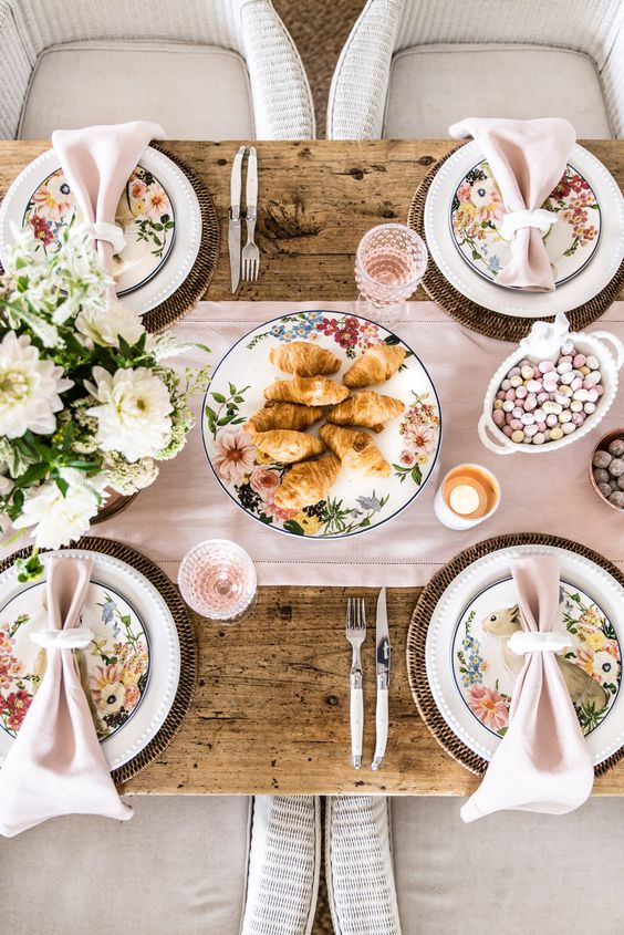 a chic pastel Easter tablescape with a pink runner and napkins, floral plates, woven chargers, white blooms and pink glasses