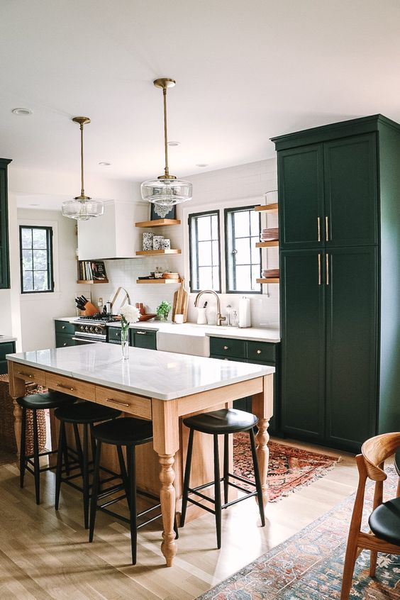 a chic retro kitchen in hunter green, with a table as a kitchen island, glass lamps and tall black stools