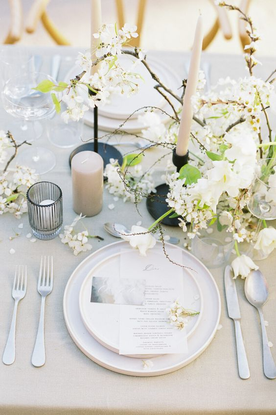 a chic spring tablescape with white blooming branches, candles, white porcelain, simple cutlery and glasses