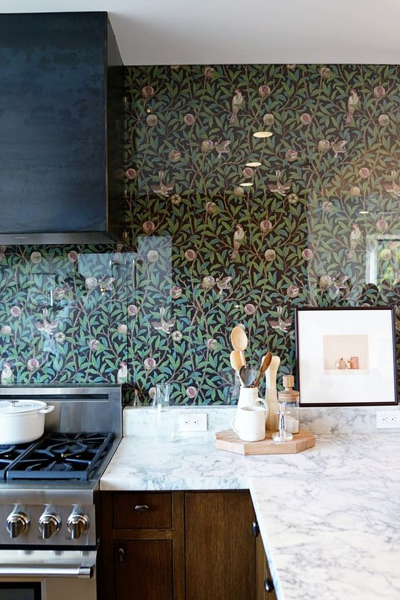 a chic vintage kitchen with stained cabinets, a black hood, white stone countertops, floral wallpaper and a glass cover to keep it in order
