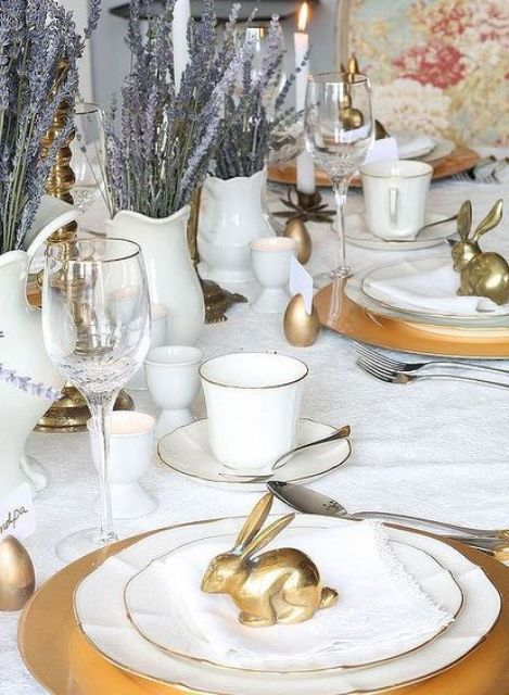 a classic Easter tablescape with white linens and porcelain, gold bunny figurines, lavender, candles and glasses