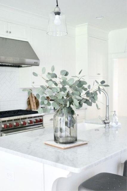 a classic spring centerpiece of a smoke glass vase and eucalyptus is always a cool idea to rock