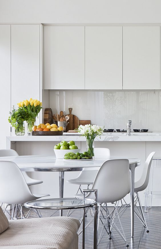 a clean minimalist kitchen in off-white, with a glass backsplash, an eating zone with a round table and cool chairs is very stylish