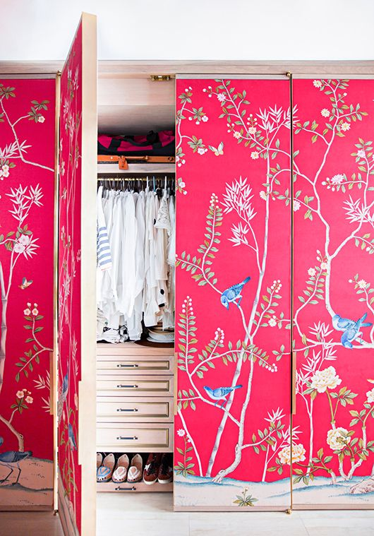 a closet covered with pink floral wallpaper to make an accent of it and bring some color to the space