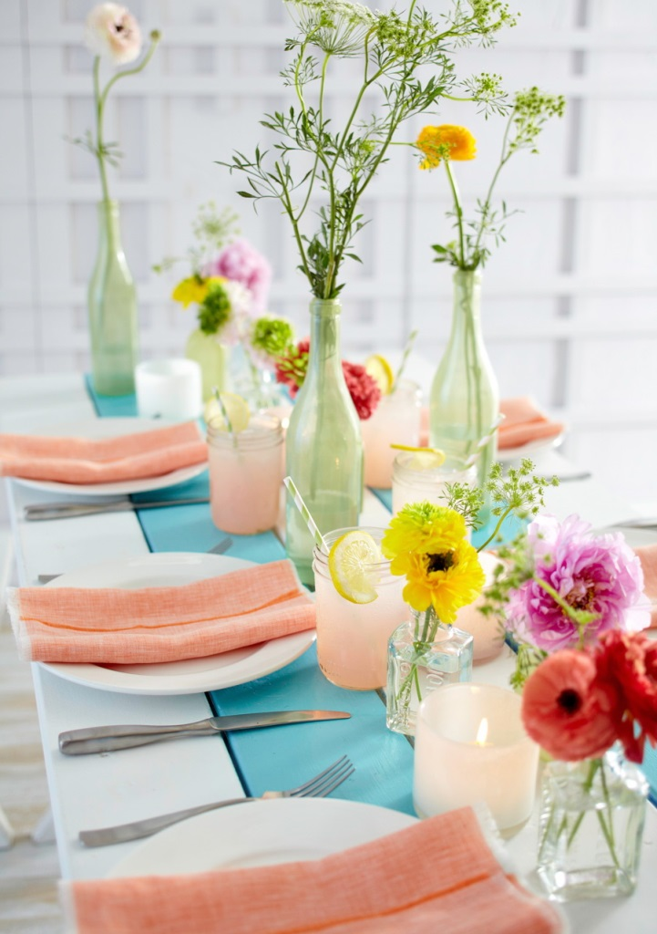 a cluster centerpiece with pastel green vases and bright blooms and greenery for a spring tablescape