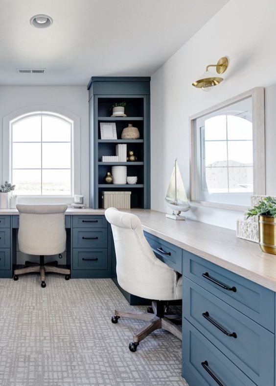 a coastal home office with blue storage units and a blue and white shared corner desk, an arched window and white chairs