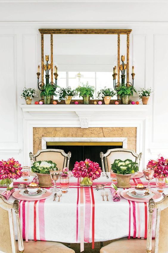 a colorful Easter table setting with striped and floral linens, bold blooms and cabbage, colorful glasses