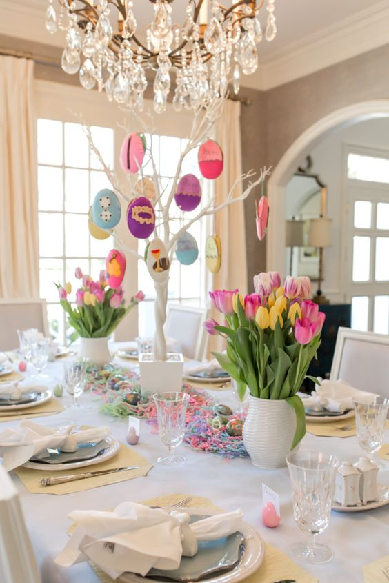 a colorful Easter tablescape with bold tulips, a funny Easter tree as a centerpiece, colorful yarn and pastel placemats