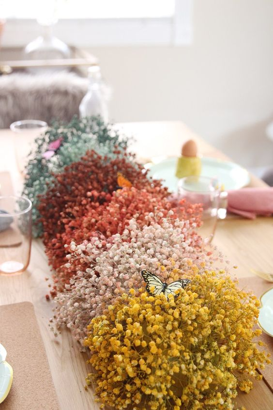 a colorful baby's breath table runner with faux butterflies is a pretty idea for spring or Easter, it looks whimsy and bold