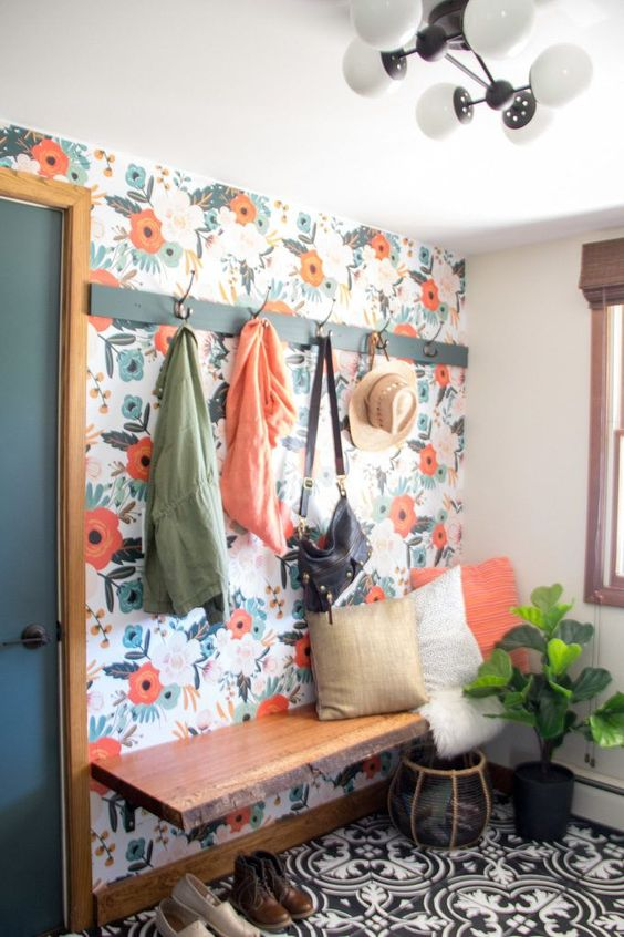 a colorful boho mudroom with a bright floral wall, a floating bench, printed tiles, a mid-century modern chandelier