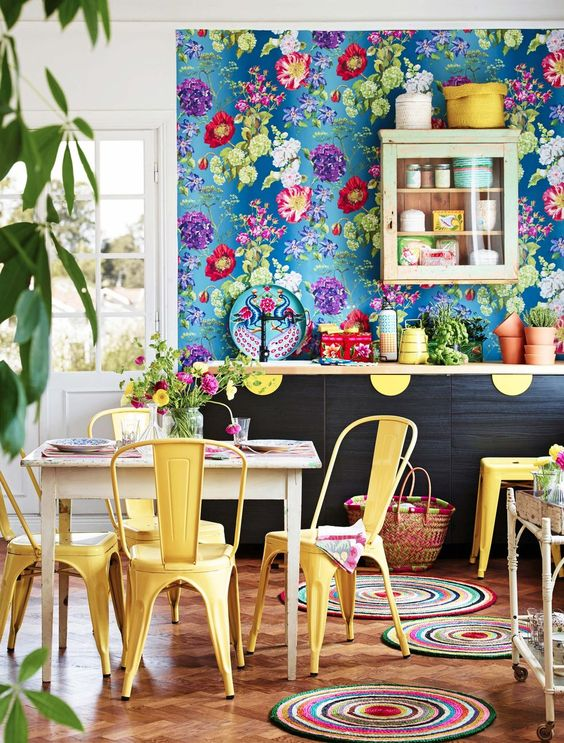 a colorful kitchen with a blue floral wall, yellow chairs and yellow touches that add fun and color to the space