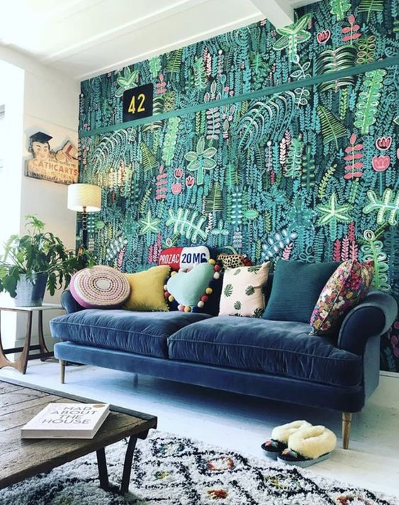 a colorful living room with a super bold botanical wall, a navy sofa and colorful pillows, bright textiles and potted greenery