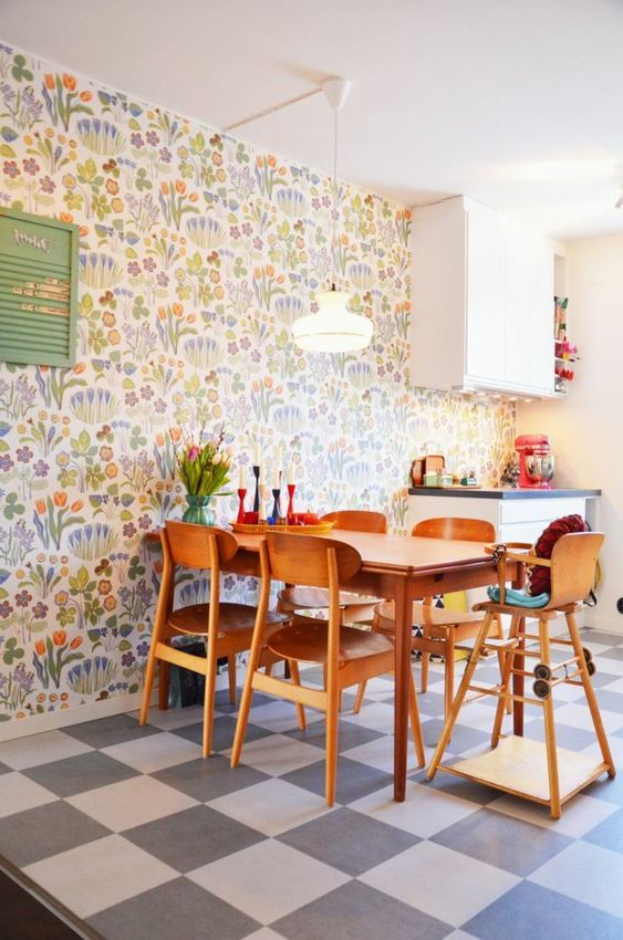 a colorful modern kitchen and dining zone accented with colorful floral wallpaper and with bright accessories for fun