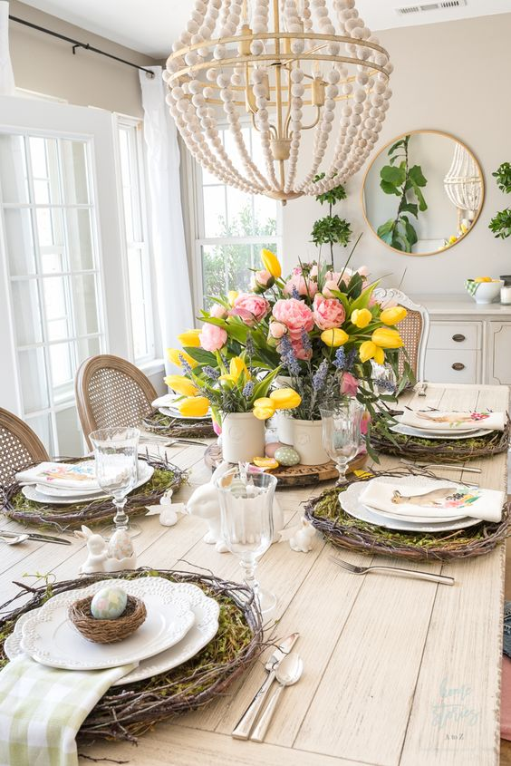 a colorful rustic Easter tablescape with vine wreaths and moss, nests with eggs, bunnies, bold blooms and greenery