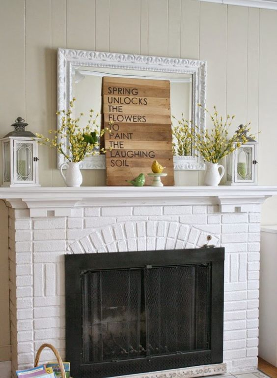a colorful vintage mantel with yellow blooming branches in jugs, bird figurines, candle lanterns and a plaque sign