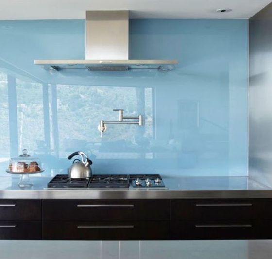 a contemporary black kitchen with stainless steel countertops and a blue glass backsplash plus stainless steel fixtures