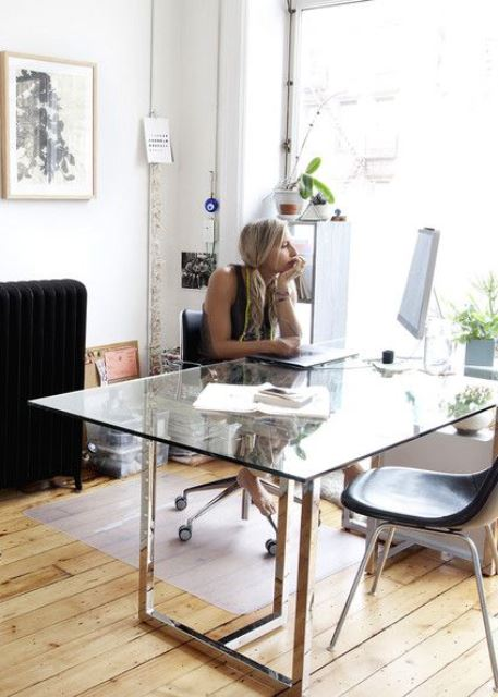 a contemporary home office with a metal and glass desk, a couple of chairs and some potted plants to refresh the space