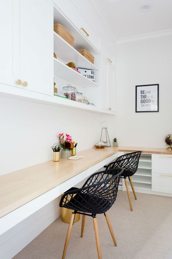 a contemporary home office with a wall storage unit, a corner desk with storage units and black chairs, an artwork and baskets