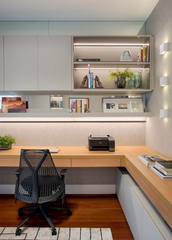 a contemporary home office with a wall storage unit with closed and open compartments, an open shelf, a corner desk and built-in lights