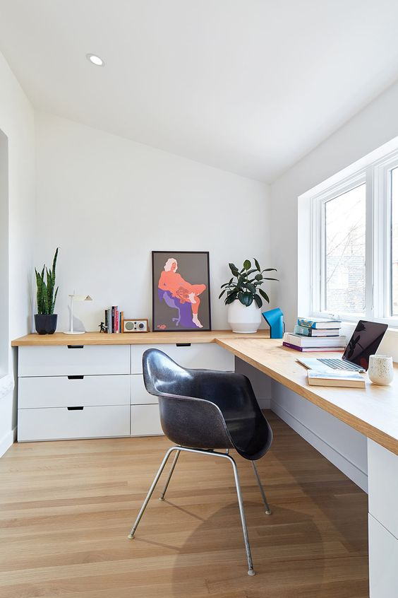 a contemporary home office with white storage units and a light stained corner desk on them, with books and plants