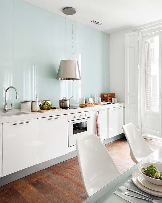 a contemporary white kitchen with an aqua blue glass backsplash, a large pendant lamp over it and a dining space here