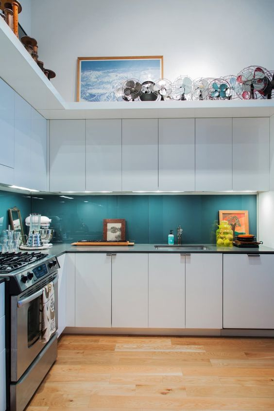 a contemporary white kitchen with black countertops and a teal glass backsplash plus built-in lights and a shelf on top