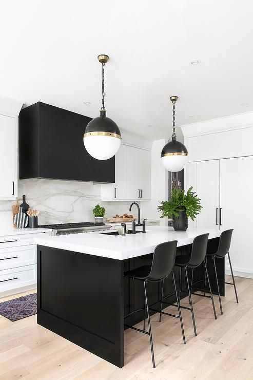 a contrasting black and white kitchen with a black hood and island, black stools and pendant lamps on chains is wow
