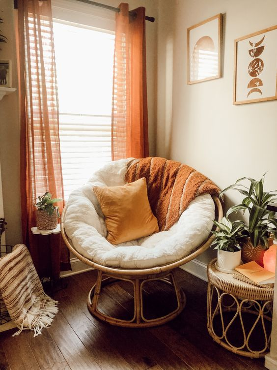 a cool boho reading space with a papasan chair with pillows and a blanket, a rattan table with potted plants and bright curtains