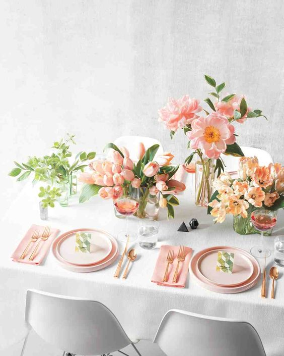 a cool spring tablescape with color - pink plates, napkins and blooms, greenery and rose gold cutlery is very modern and fresh