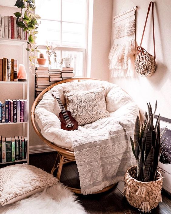 a cozy boho nook with a papasan chair with pillows, potted plants, a macrame hanging, stacks of books and a small guitar