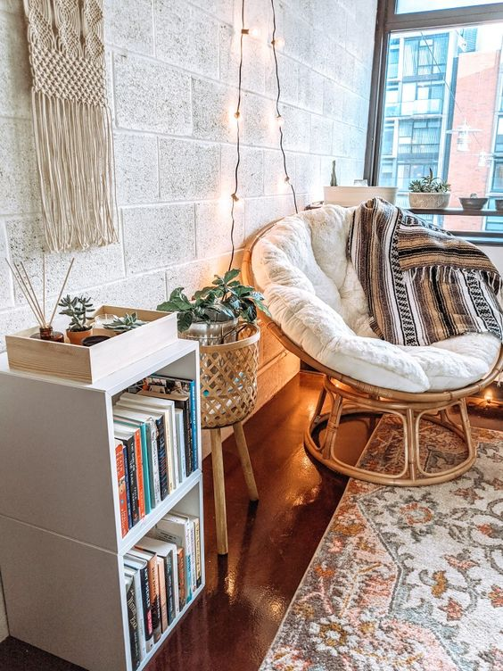 a cozy boho reading nook organized with a papasan chair with a blanket, a boho planter with greenery, a bookshelf, lights and a macrame piece