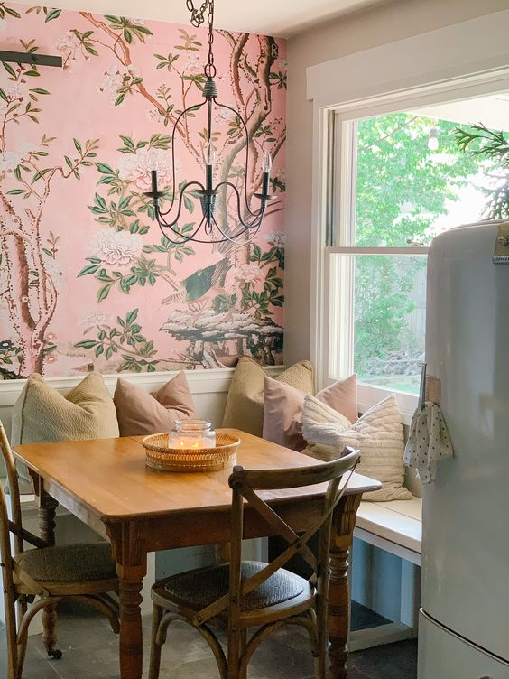 a cozy dining nook with bright pink floral wallpaper, a corner seating, a wooden chair and a vintage chandelier