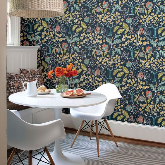 a cozy dining space with a built-in bench, a couple of chairs and a round table, a pendant lamp plus moody botanical wallpaper