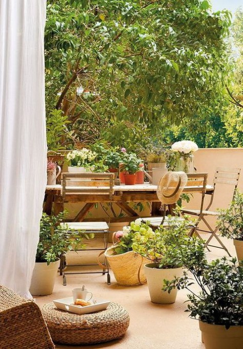 a cozy earthy tone terrace with a vintage wooden table and folding chairs, potted blooms and greenery and woven pieces