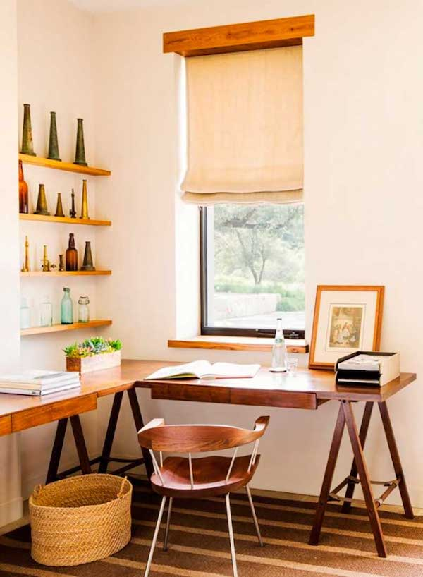 a cozy farmhouse home office with a corner trestle desk, a wooden chair and a basket, floating shelves with vintage bottles