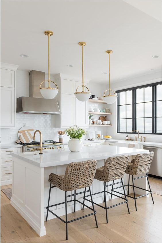 a cozy farmhouse kitchen with white cabinets, wicker chairs, a white subway tile backsplash and refined pendant lamps